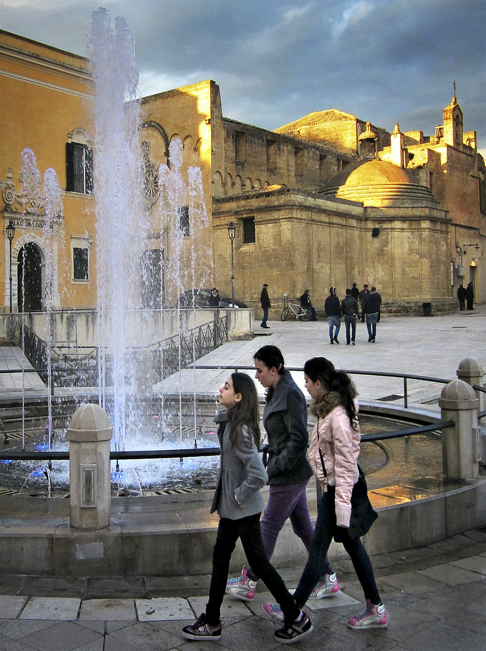 woman in gray coat standing near fountain
