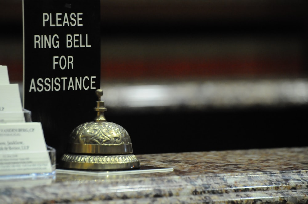 gold bell on brown wooden table