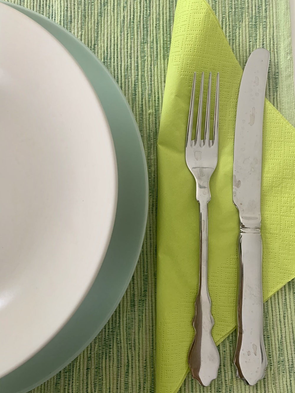 silver fork and bread knife on white ceramic plate