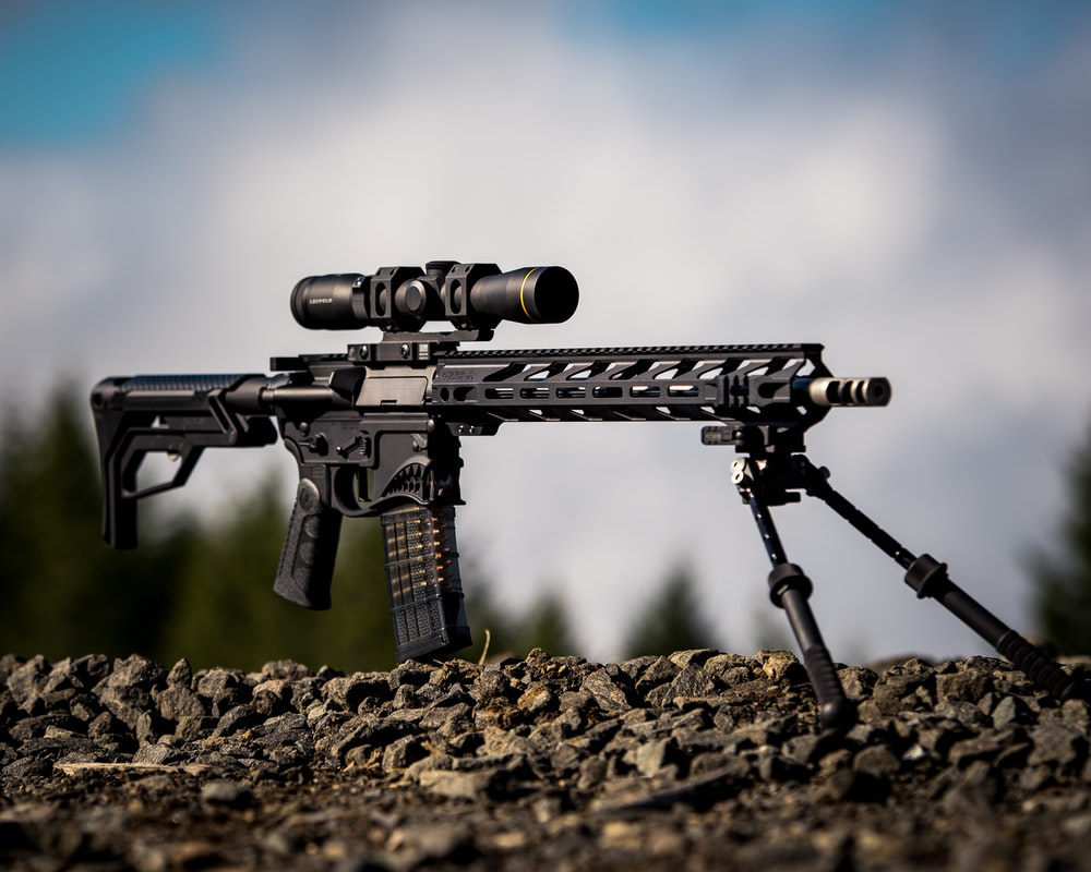 black rifle with scope on brown soil