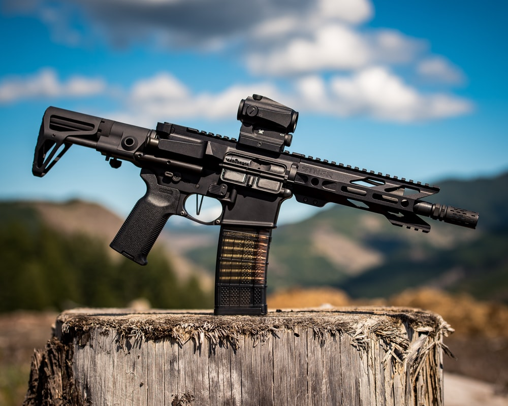 black assault rifle on brown wooden log