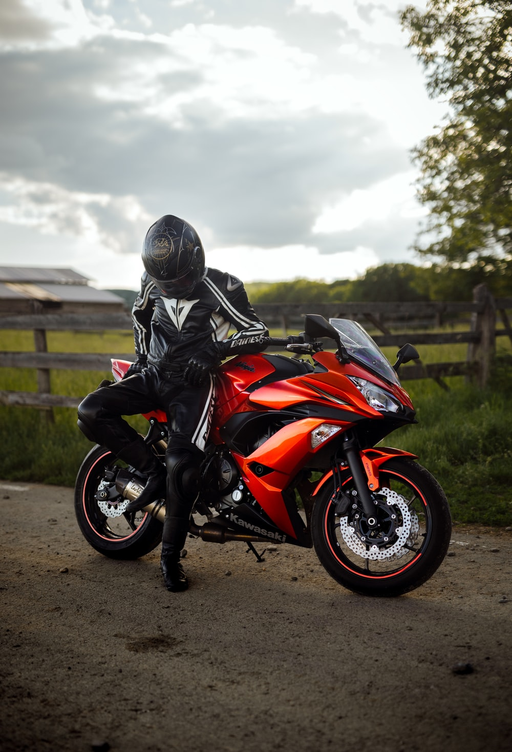 man in black helmet riding orange sports bike
