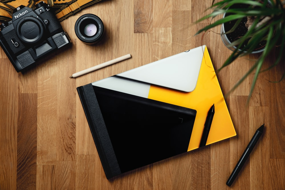 black ipad on yellow folder