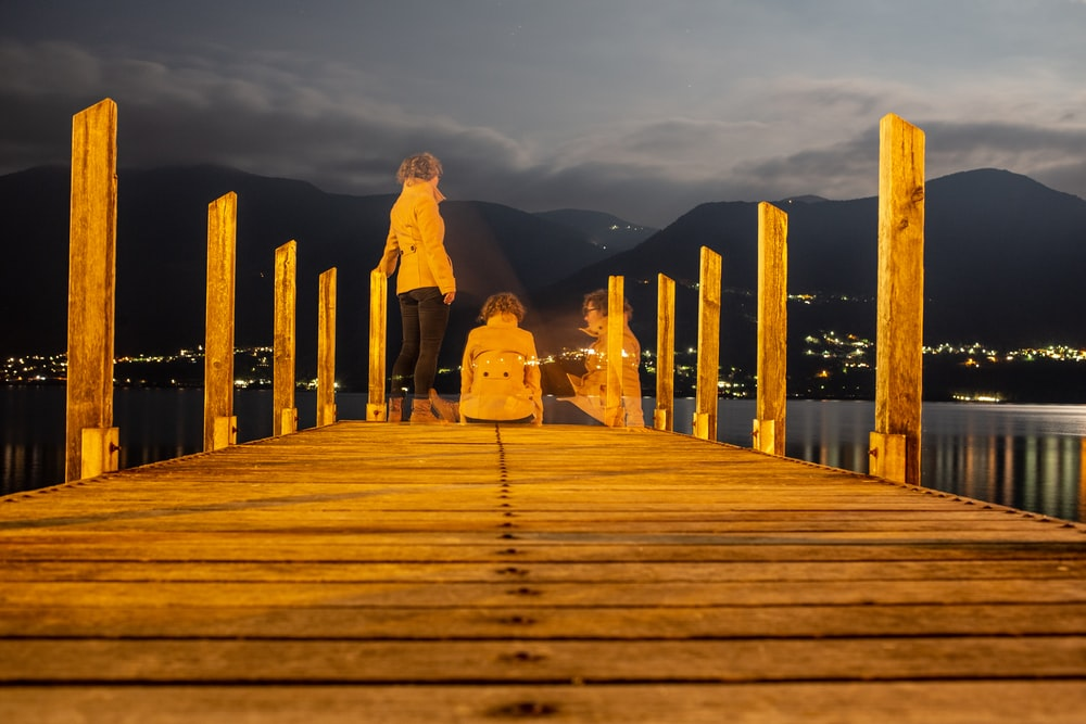 couple walking on wooden dock during daytime