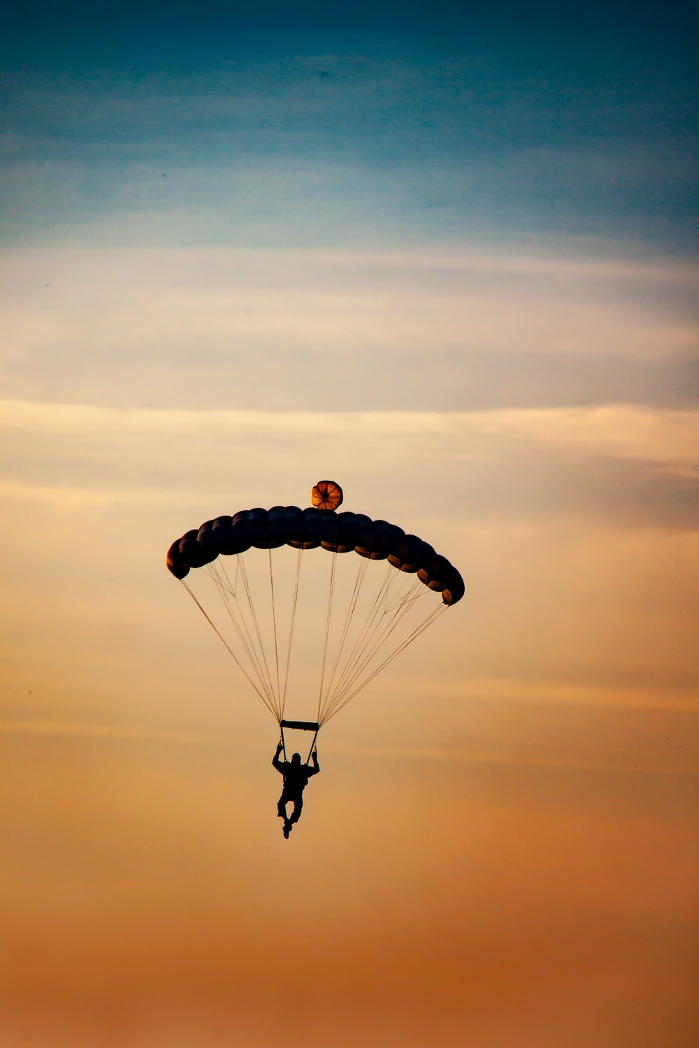person in parachute under white clouds during daytime