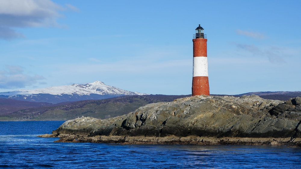 red and white lighthouse on brown and green mountain under blue sky during daytime
