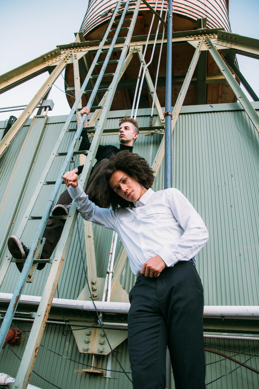 man in white dress shirt and black pants sitting on white metal ladder during daytime