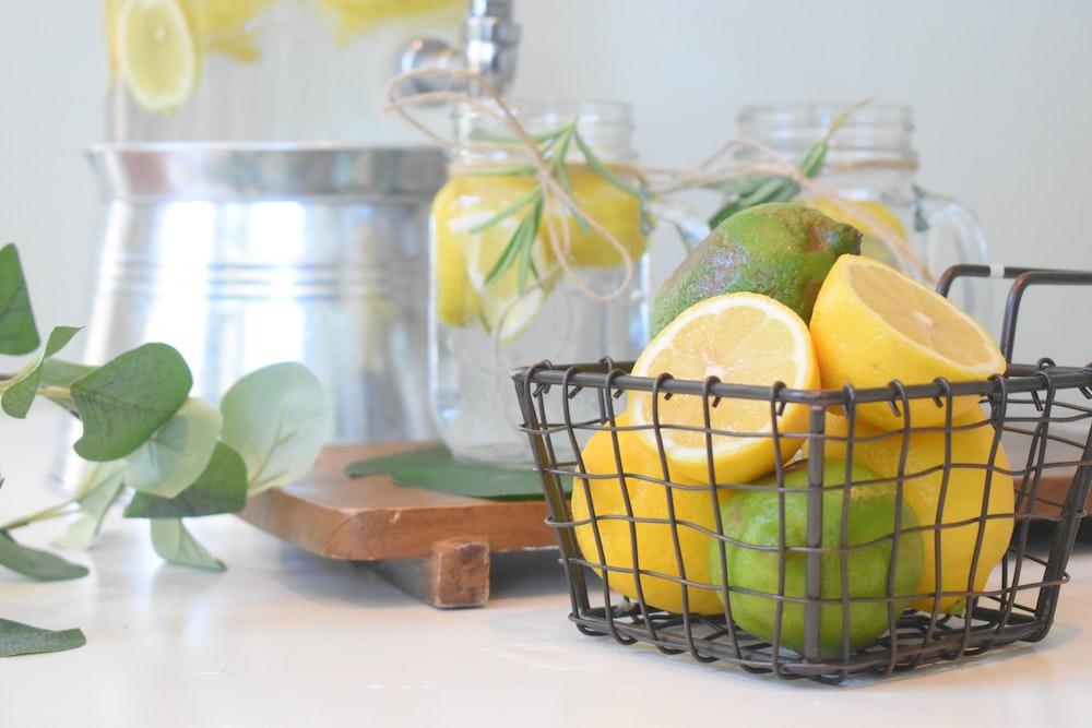 green lemon fruit in black metal basket