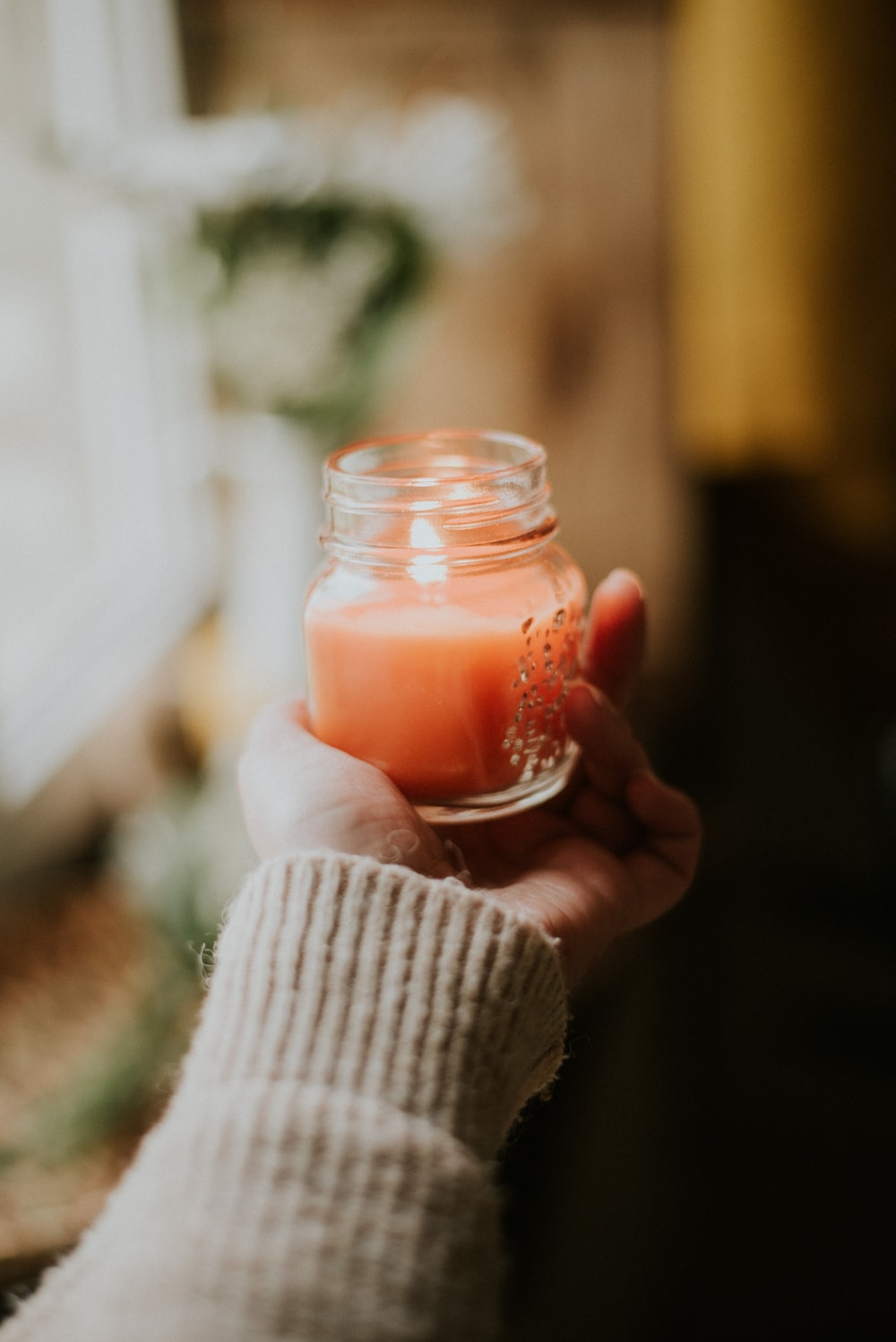 person holding clear glass candle holder with red candle