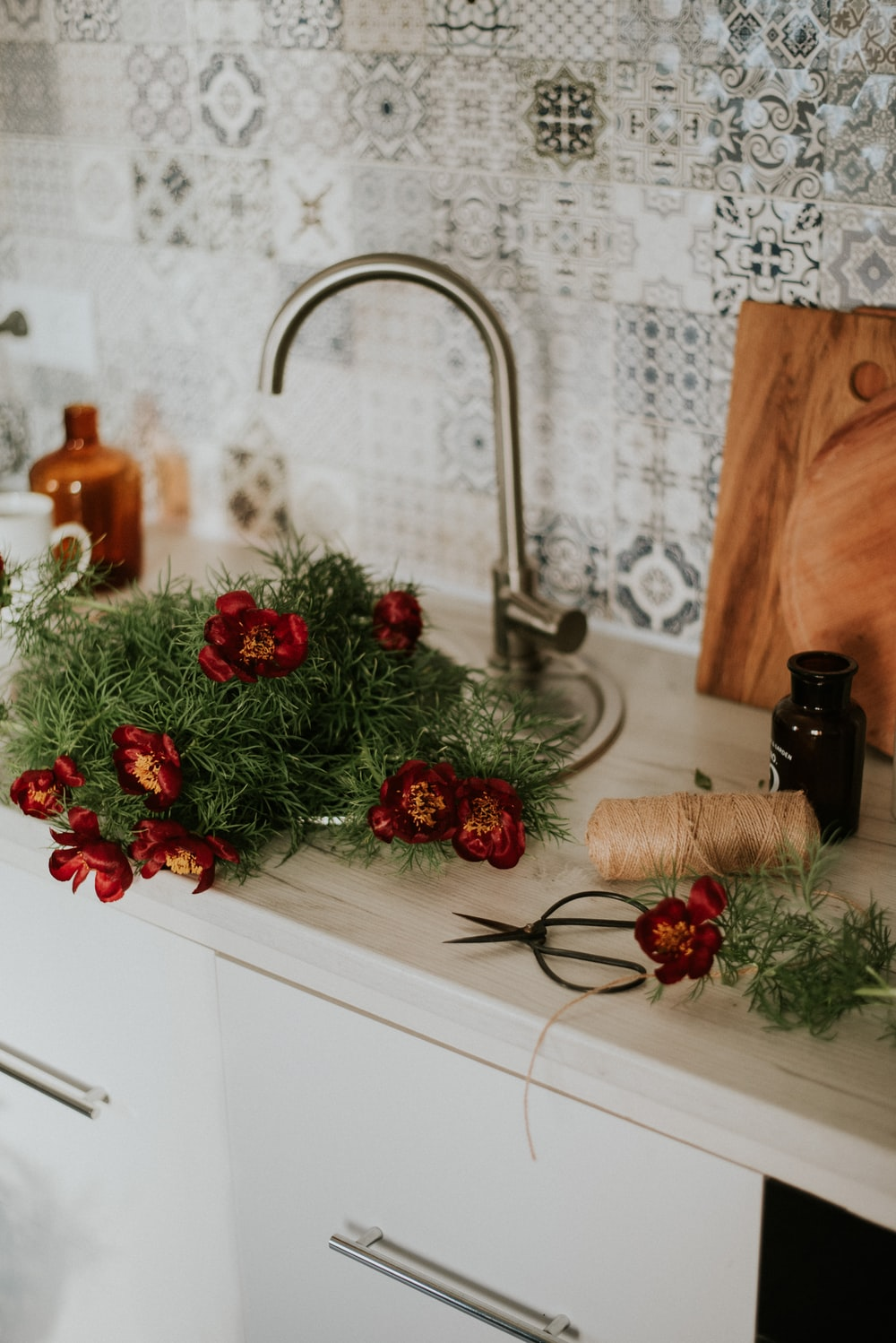 green and red christmas wreath on brown wooden chopping board