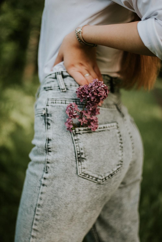 woman in gray denim jeans holding pink flower bouquet