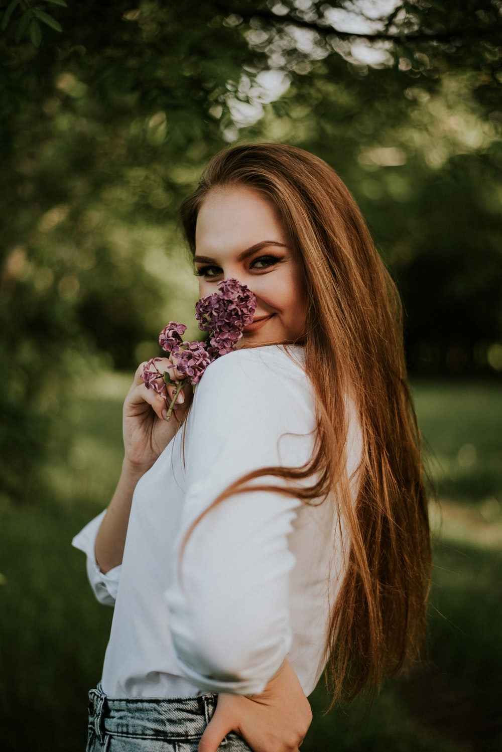 woman in white long sleeve shirt holding pink flowers