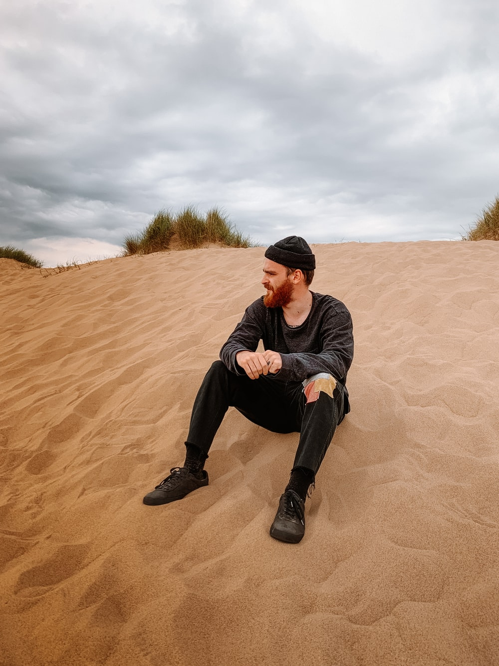 man in black jacket and black pants sitting on brown sand during daytime