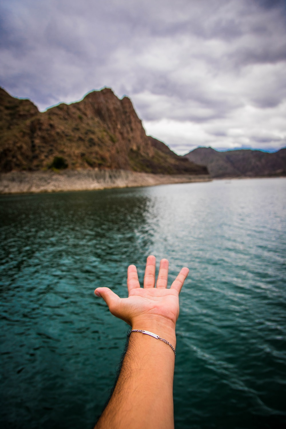 person with green manicure near body of water during daytime
