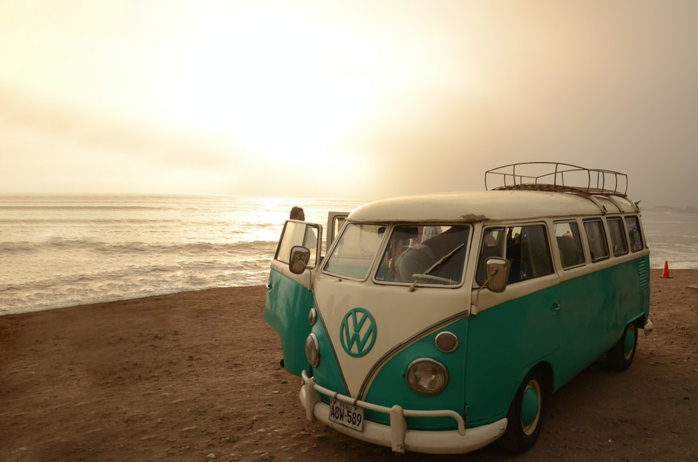 white and blue volkswagen t-1 on beach shore during daytime