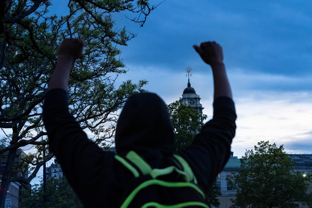 person in black and green jacket raising right hand