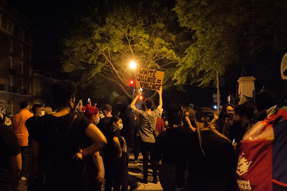 people standing and raising their hands during nighttime