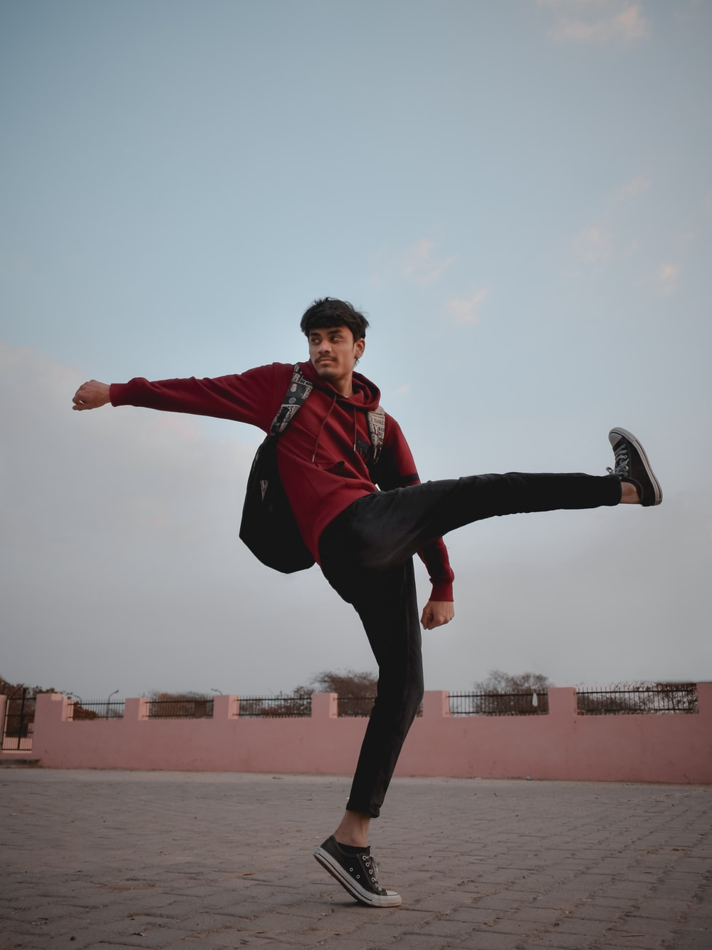 man in red and black jacket and black pants jumping on mid air during daytime