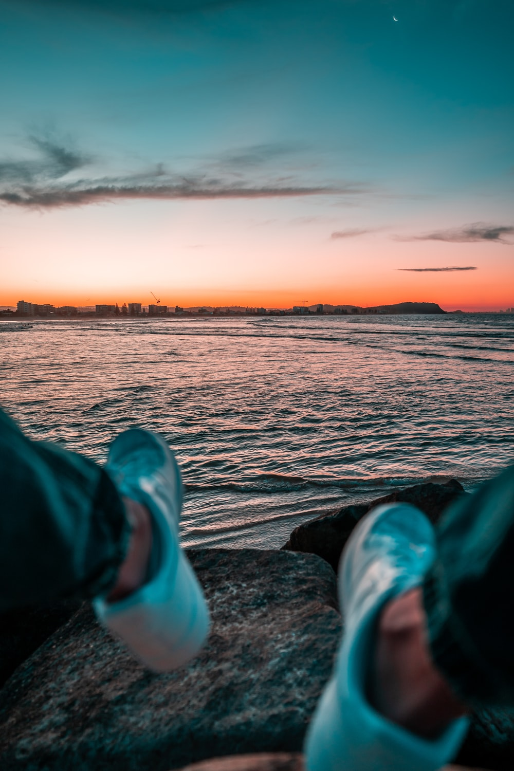 person in green pants and white sneakers sitting on rock near body of water during sunset