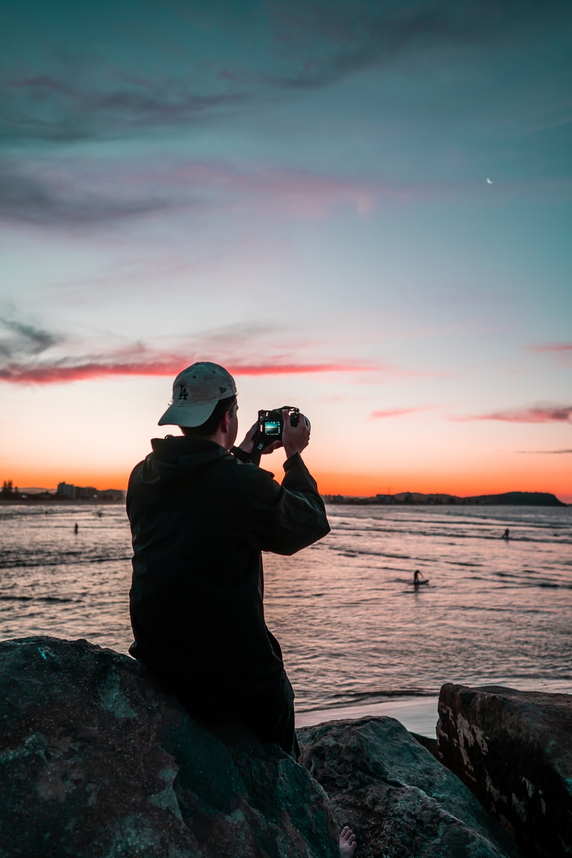 man in black jacket taking photo of sunset
