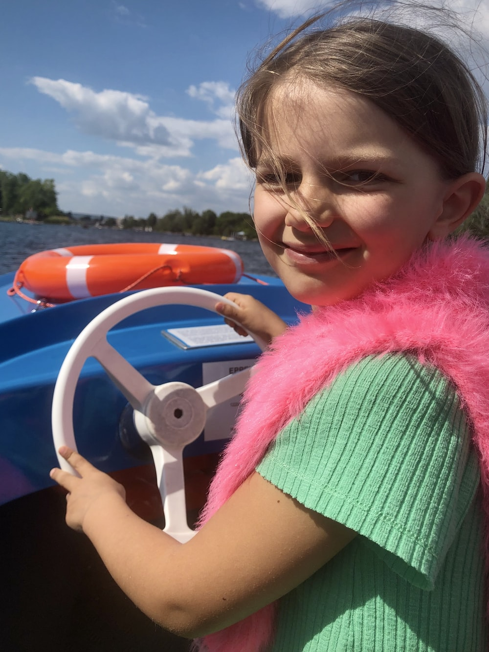 girl in pink wings riding on blue inflatable ring