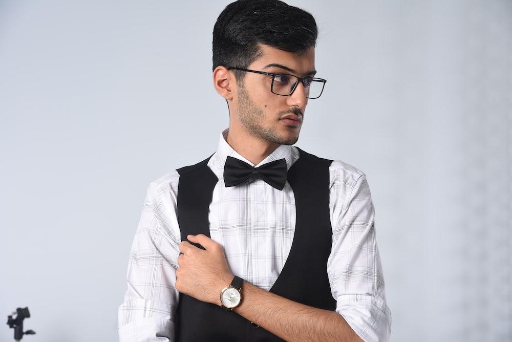 man in white and black button up shirt wearing black framed eyeglasses