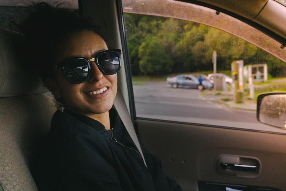 woman in black jacket wearing black sunglasses sitting inside car
