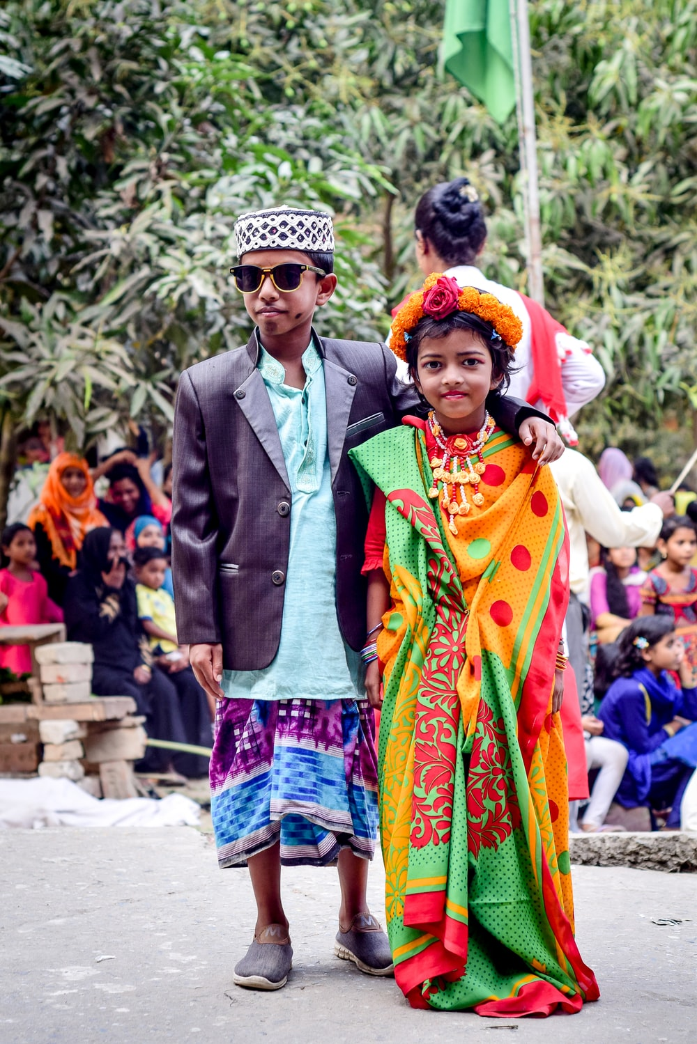man in green suit jacket and woman in green and yellow sari dress