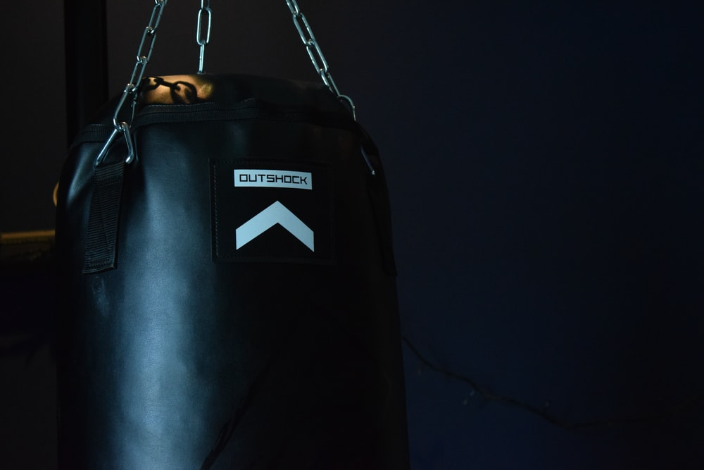 black leather boxing gloves hanging on white metal bar