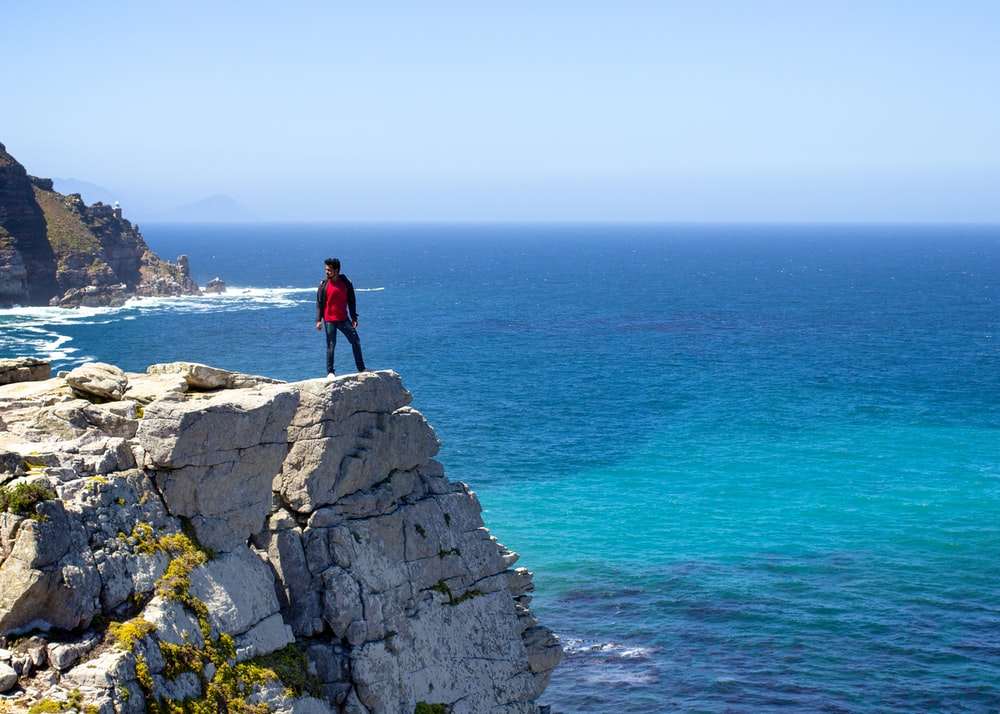 man in black jacket standing on gray rock formation near blue sea during daytime