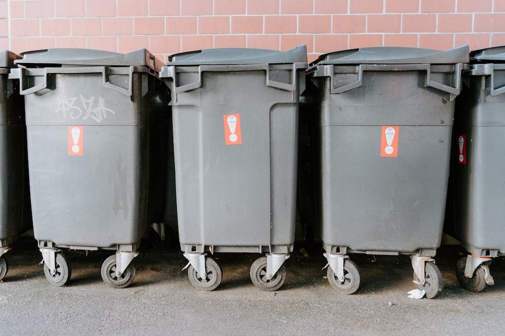 black garbage bins on sidewalk