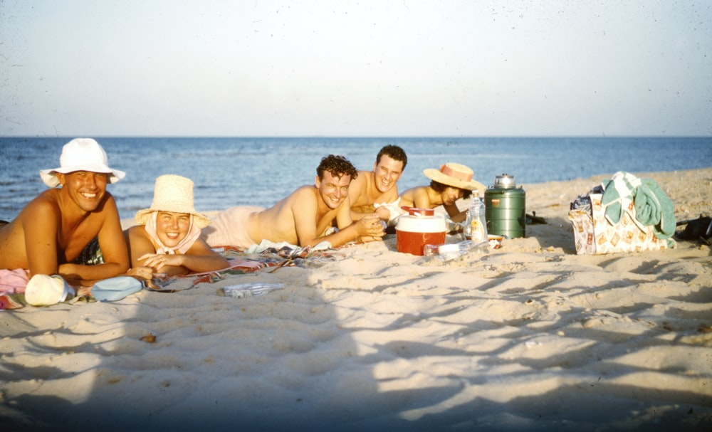 3 women sitting on sand near body of water during daytime