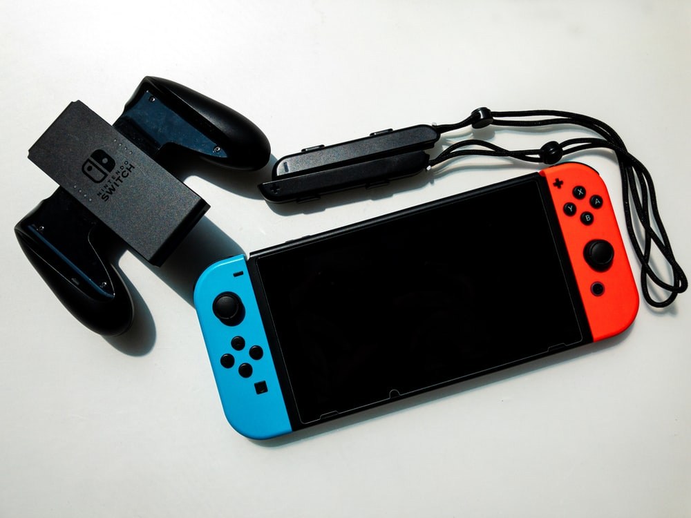 white nintendo switch beside black usb flash drive