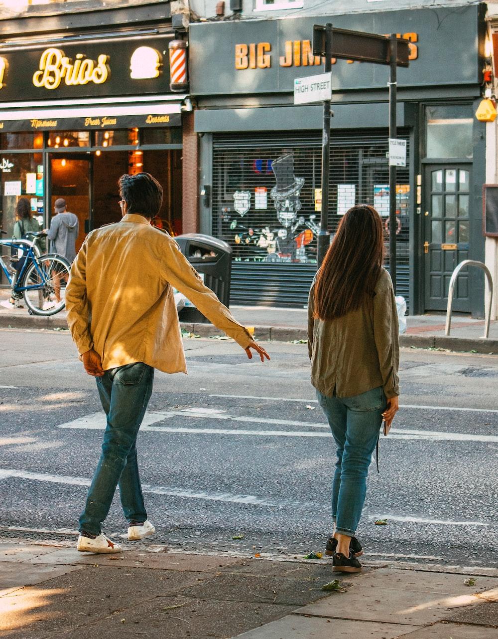woman in brown jacket and blue denim jeans walking on sidewalk during daytime