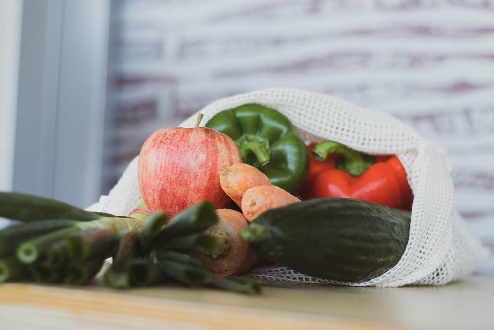 red tomato beside green vegetable on white table