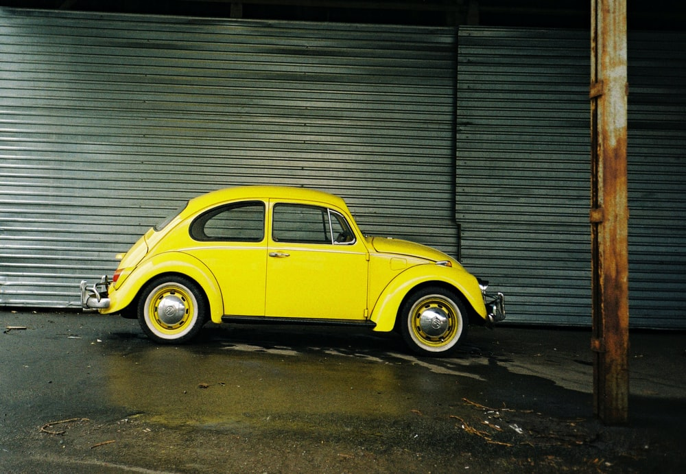 yellow volkswagen beetle parked beside gray roll up door
