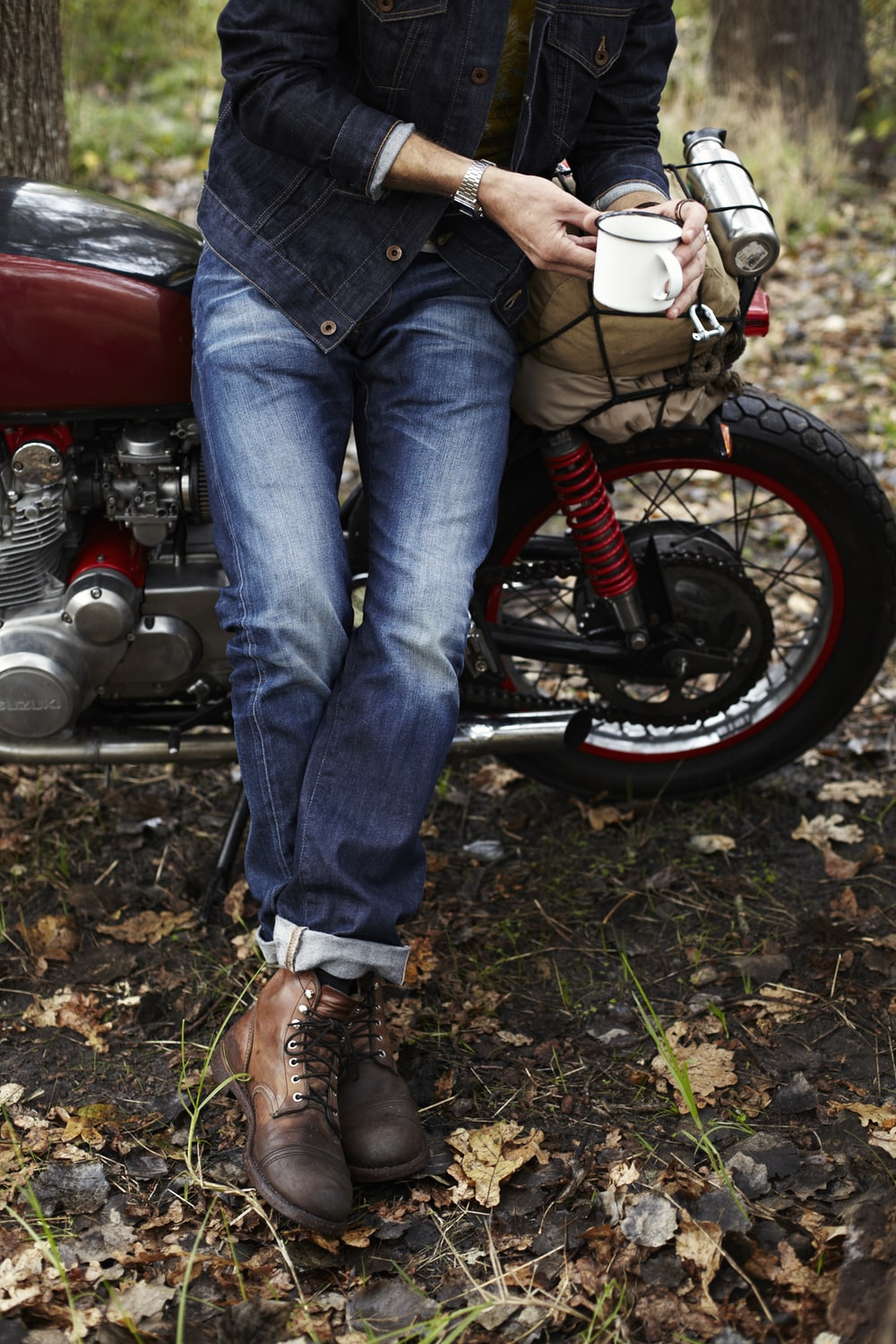 person in blue denim jeans and white sneakers sitting on red motorcycle