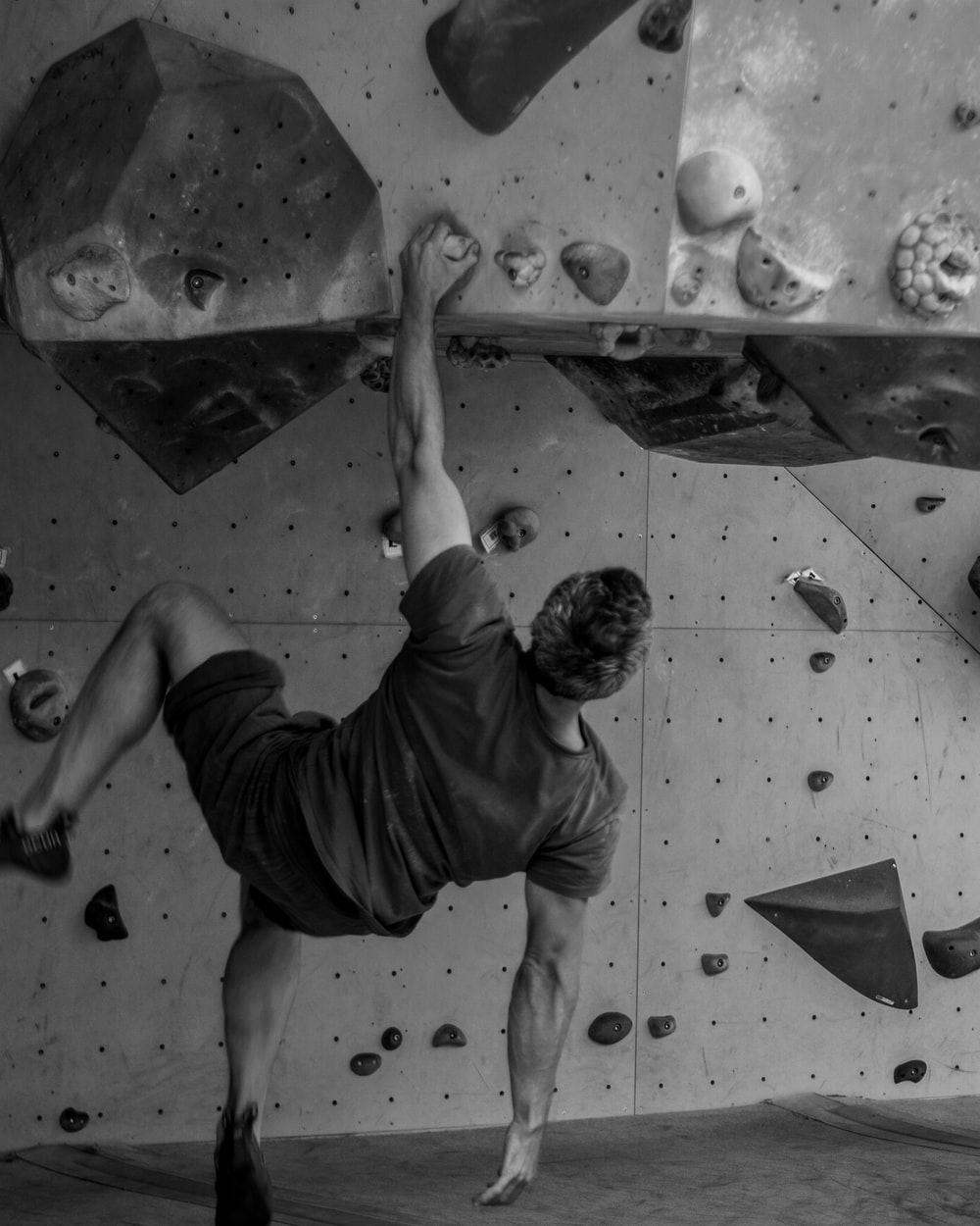 grayscale photo of man in t-shirt and shorts climbing on wall