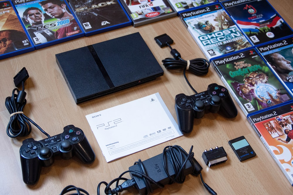 black sony ps 4 game controller on brown wooden table