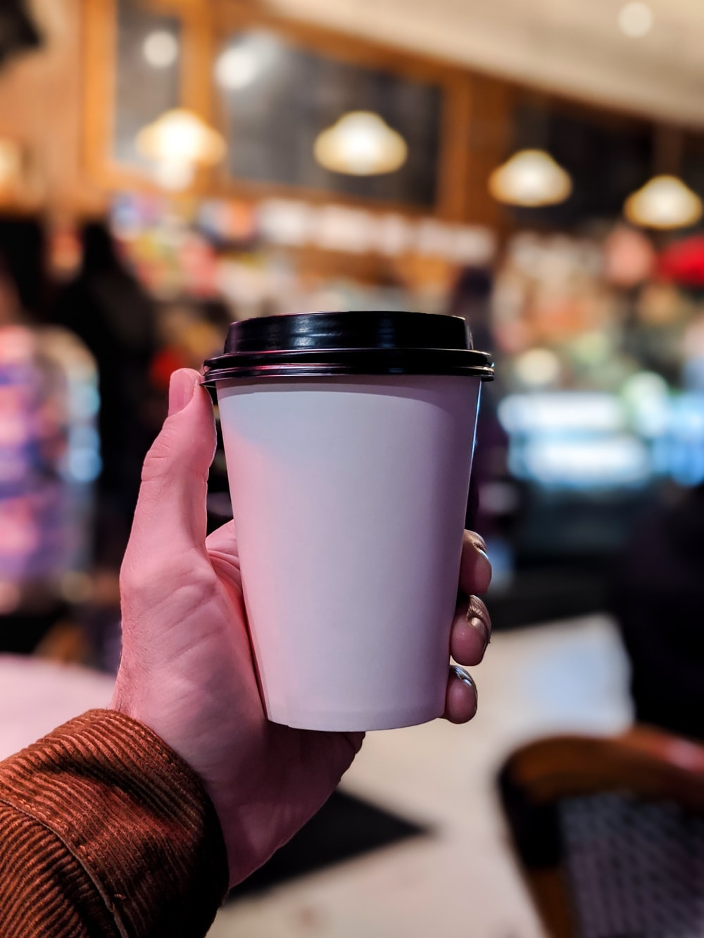 person holding white and black disposable cup