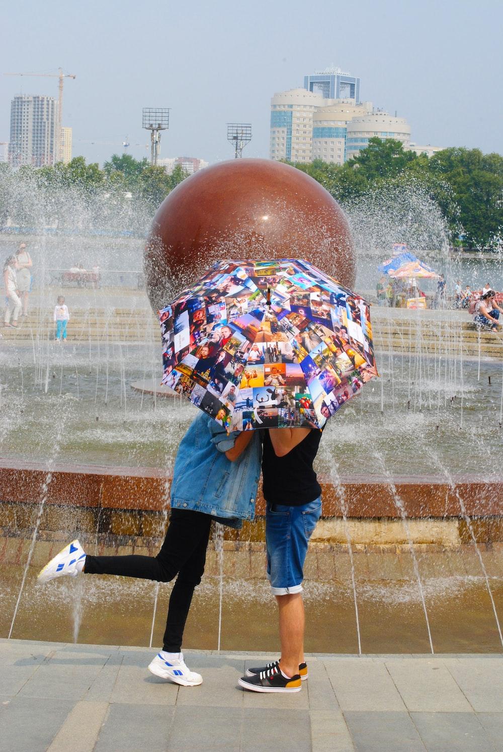 woman in blue denim jacket standing near water fountain