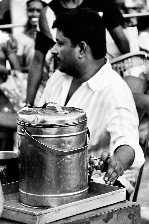 man in white dress shirt holding stainless steel bucket
