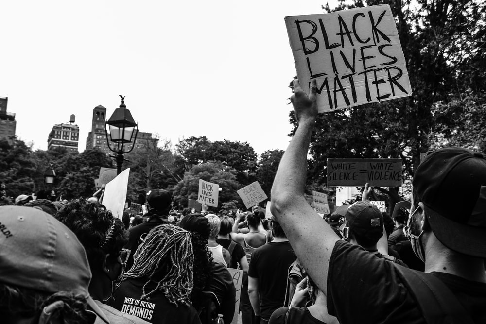 grayscale photo of people holding square board