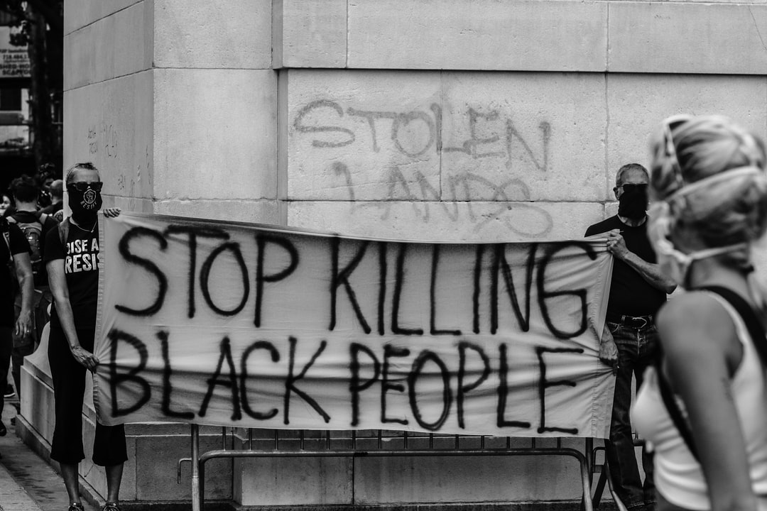 Two Men Holding Up A Sign Asking For the Police To Stop Killing Black People. - unsplash