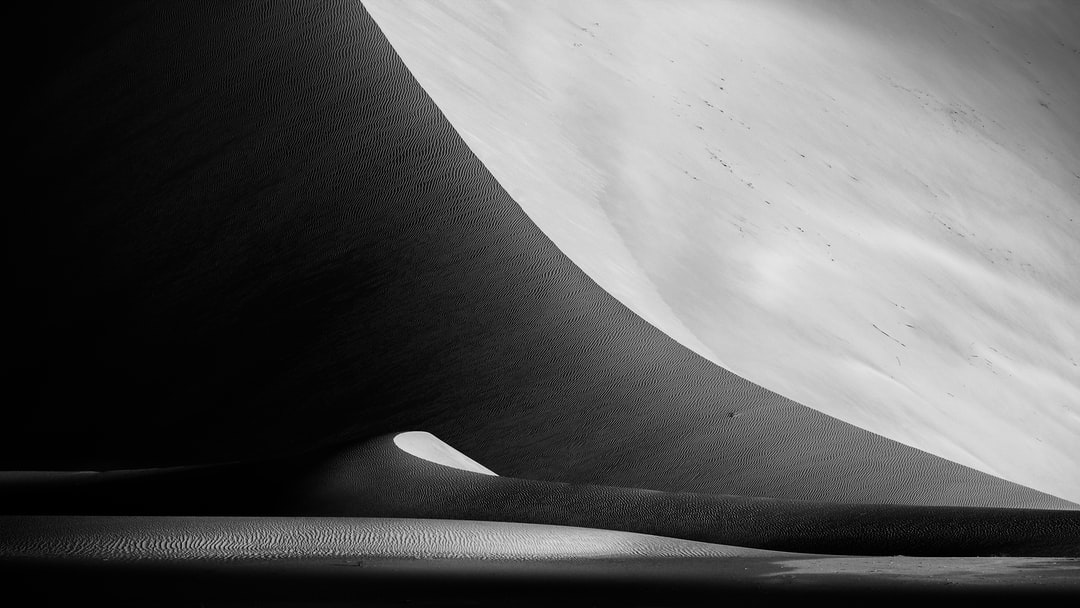 Grayscale Photo of Sand Dunes - unsplash