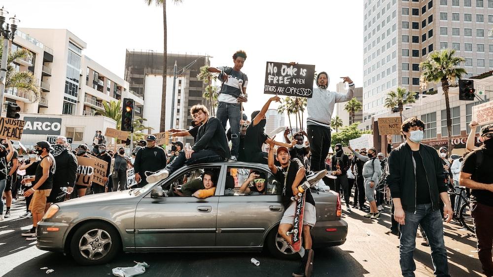 people standing beside black car during daytime