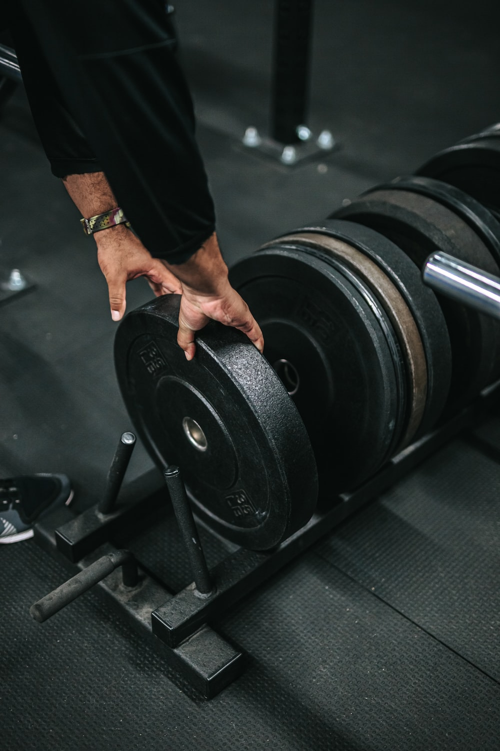 person holding black dumbbell in black gym