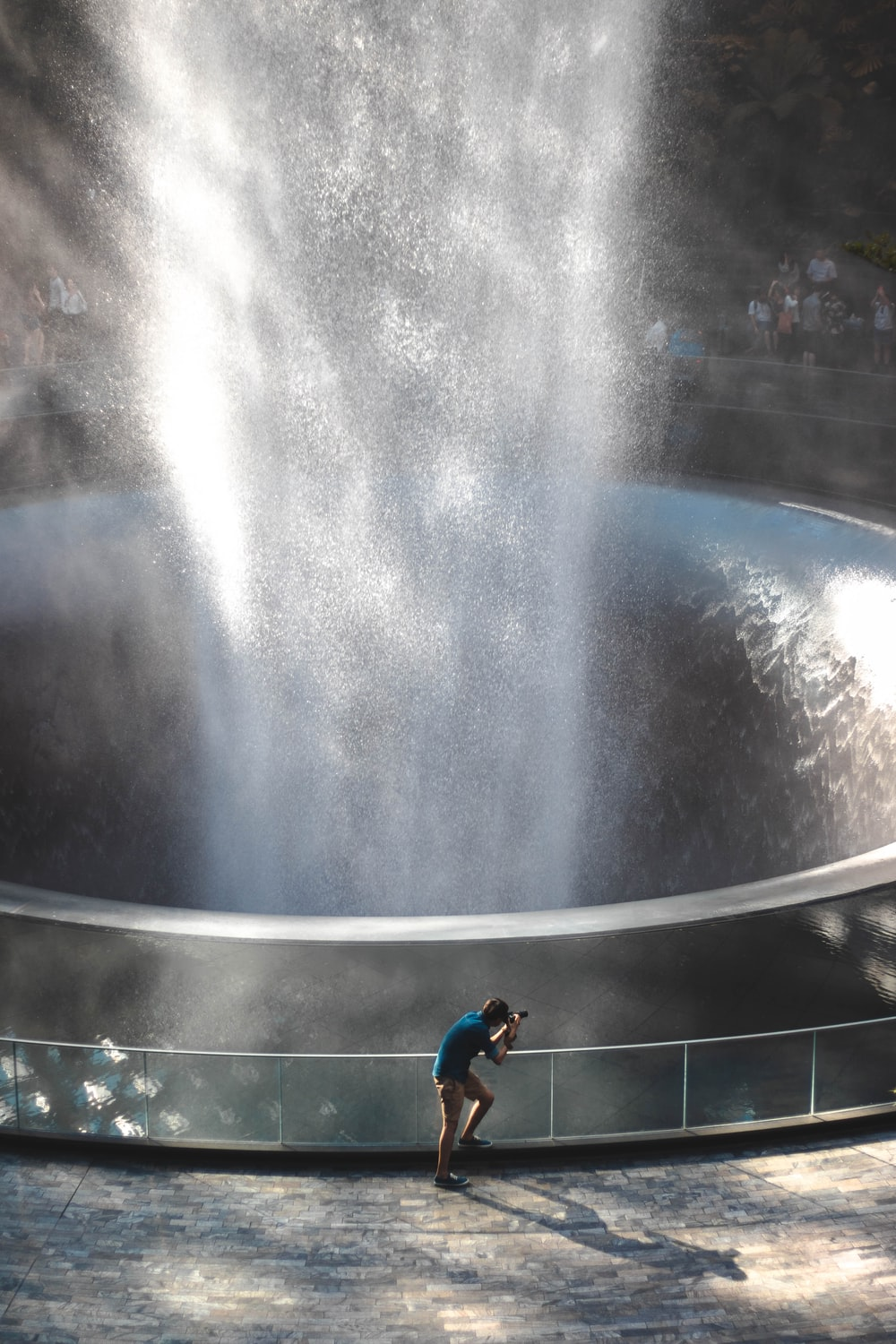 boy in blue t-shirt and black shorts standing on water fountain during daytime