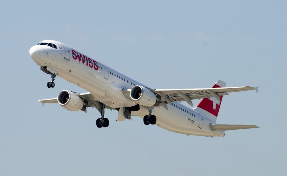 white and red passenger plane flying during daytime