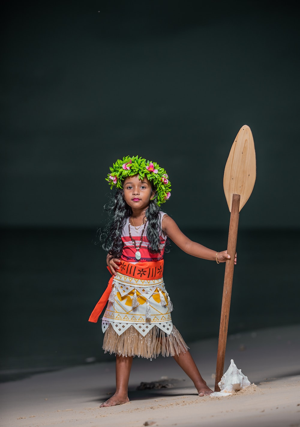 woman in red and brown dress holding brown wooden stick